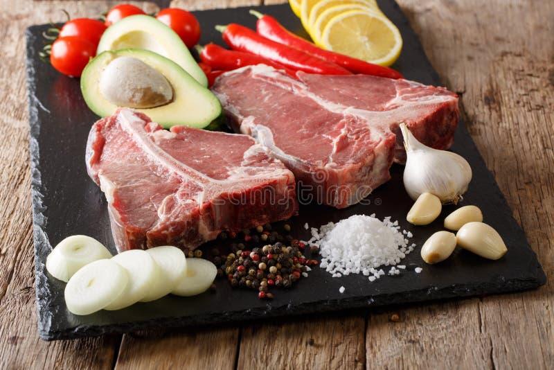 Bistecca di manzo cruda della lombata con il primo piano degli ingredienti orizzontale fotografia stock