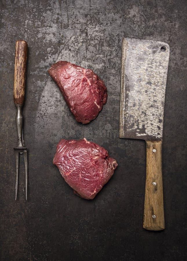 Bistecca di manzo cruda fresca con la mannaia di carne sulla vista superiore del fondo rustico scuro immagini stock libere da diritti