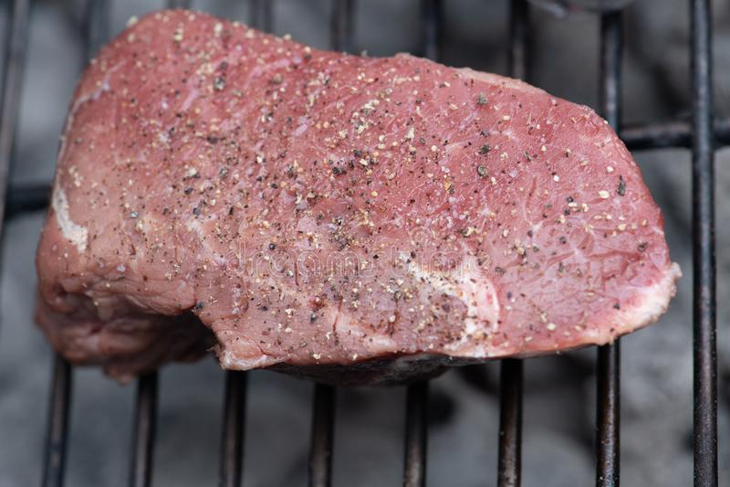 Bistecca di manzo cruda su una griglia immagini stock