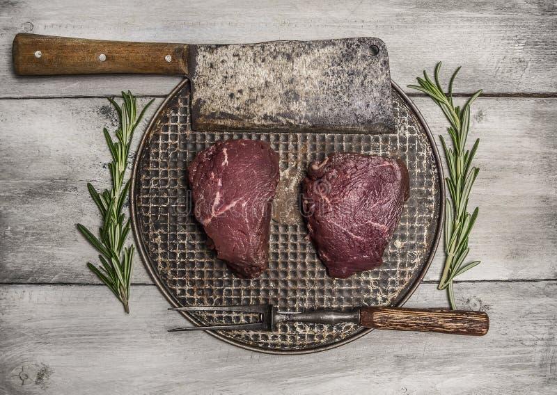 Bistecca di manzo cruda su una pentola del ferro con i rosmarini, la mannaia di carne e la forcella sulla fine di legno luminosa  immagini stock libere da diritti