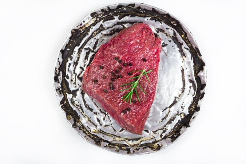 Bistecca di manzo cruda sul vecchio piatto fotografie stock
