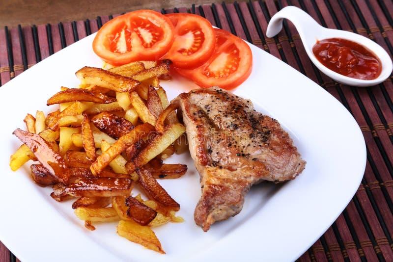 Bistecca di manzo ruspante arrostita con la patata liberamente, i pomodori e la salsa freschi su un fondo di pietra marrone immagine stock
