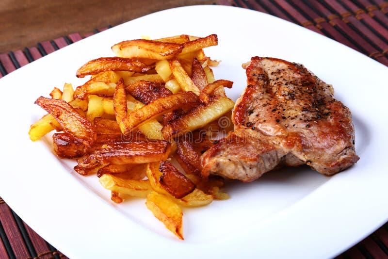 Bistecca di manzo ruspante arrostita con la patata liberamente, i pomodori e la salsa freschi su un fondo di pietra marrone immagini stock