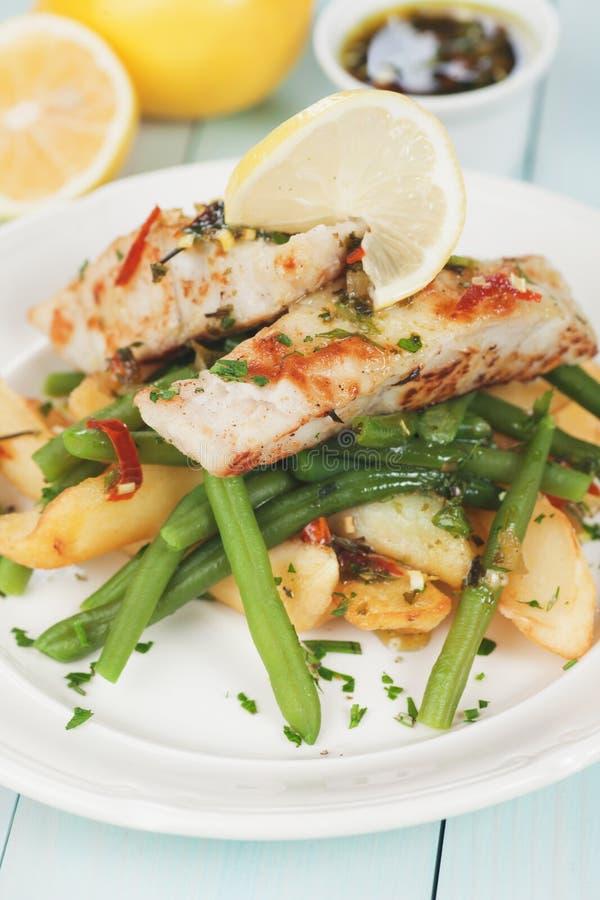 Bistecca di merluzzo con la patata ed il fagiolino fritti fotografia stock