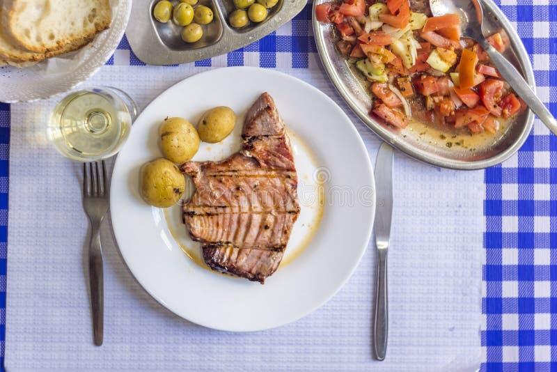 Bistecca di tonno di accompagnamento con le patate, olive, insalata del pomodoro, brea immagini stock libere da diritti