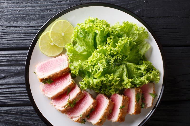 Bistecca di tonno affettata deliziosa fritta nell'impanare servito con la foglia s immagine stock