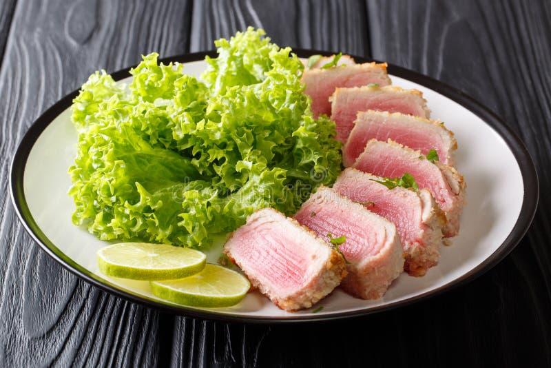 Bistecca di tonno affettata deliziosa fritta nell'impanare servito con la foglia s immagini stock libere da diritti