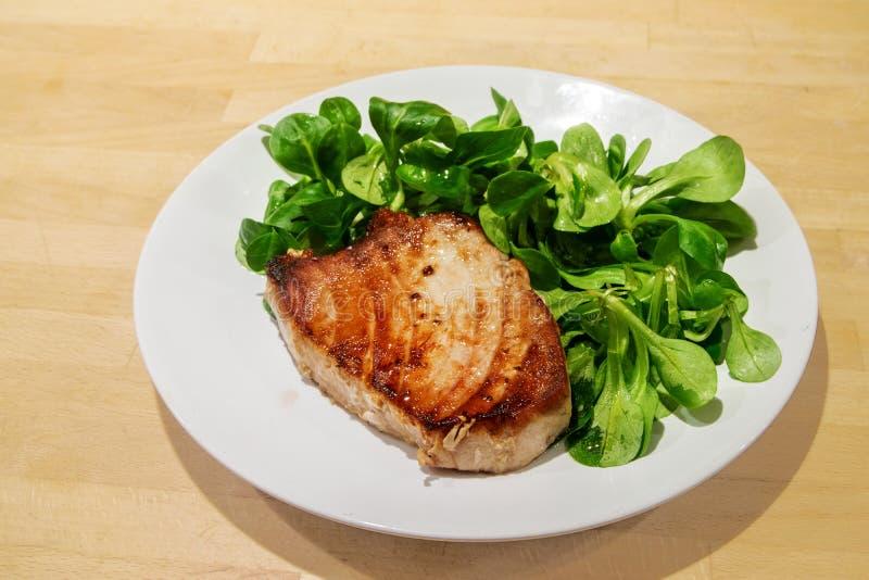 Bistecca di tonno con la valerianella su un piatto bianco su un backgrou di legno fotografie stock libere da diritti