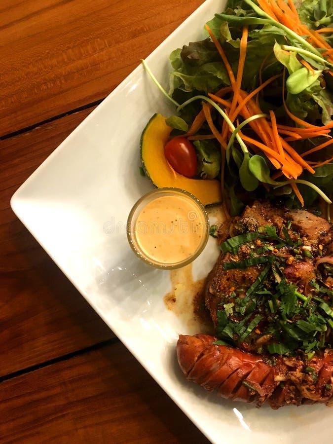 Bistecca e salsiccia della carne di maiale con salsa ed insalata di erbe piccanti con il condimento in unità di elaborazione del  fotografia stock
