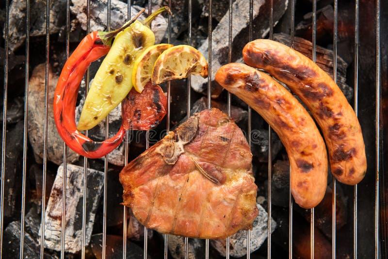 Bistecca e verdura di braciola di maiale con la salsiccia su un gril ardente del BBQ immagini stock libere da diritti