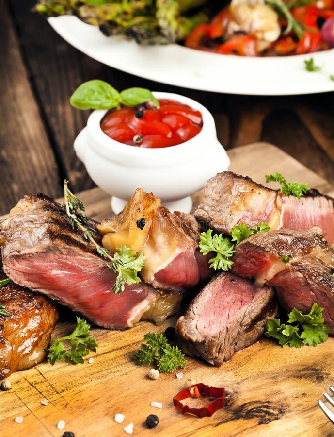 Bistecca, erbe e spezie di manzo arrostita del ribeye Vista superiore fotografie stock libere da diritti