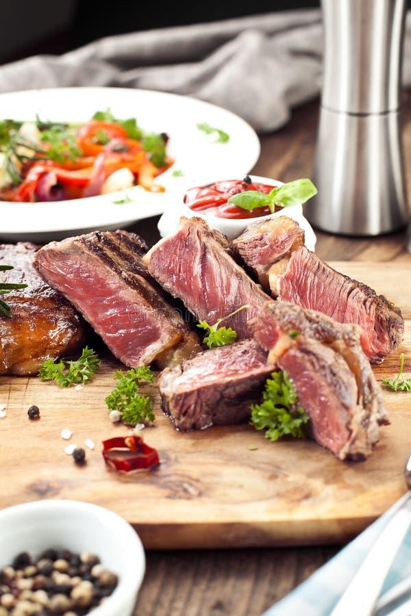 Bistecca, erbe e spezie di manzo arrostita del ribeye Vista superiore immagini stock libere da diritti