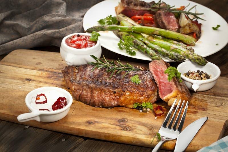 Bistecca, erbe e spezie di manzo arrostita del ribeye Vista superiore immagini stock