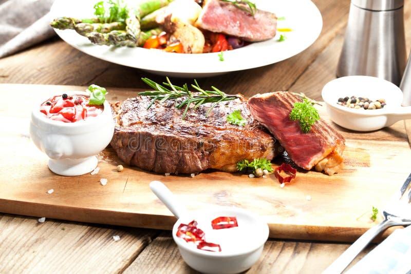 Bistecca, erbe e spezie di manzo arrostita del ribeye Vista superiore immagine stock libera da diritti