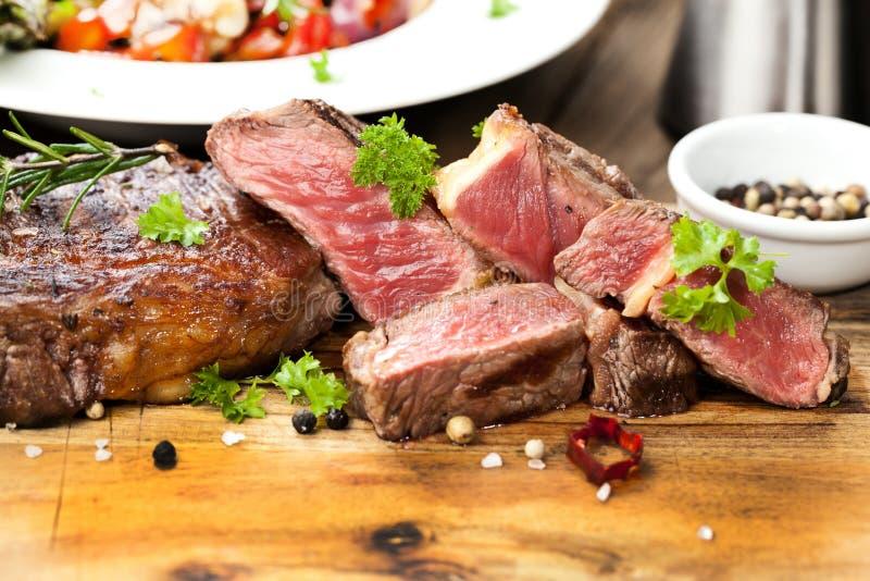 Bistecca, erbe e spezie di manzo arrostita del ribeye Vista superiore fotografia stock libera da diritti