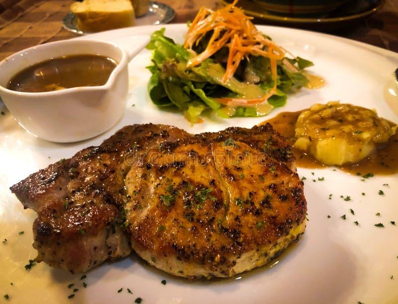 Bistecca fritta di braciola di maiale, patata ed insalata di verdure fotografia stock libera da diritti