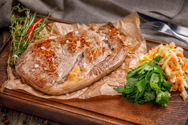 Bistecca fritta fresca deliziosa su un bordo di legno per servire con i condimenti e le erbe, un grande pezzo di carne fritta fotografia stock libera da diritti