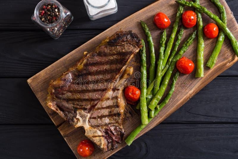 Bistecca nella lombata arrostita con asparago ed i pomodori ciliegia immagine stock