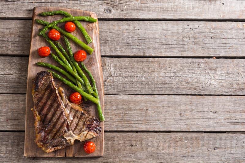 Bistecca nella lombata arrostita con asparago ed i pomodori ciliegia fotografia stock libera da diritti