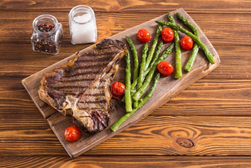 Bistecca nella lombata arrostita con asparago ed i pomodori ciliegia immagini stock