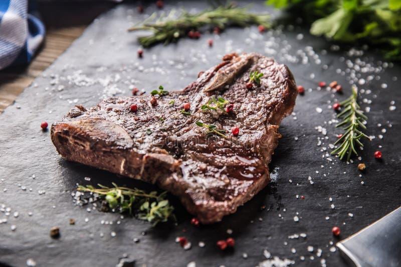 Bistecca nella lombata del manzo con il pepe ed i rosmarini del sale sulla piastrina dell'ardesia fotografie stock