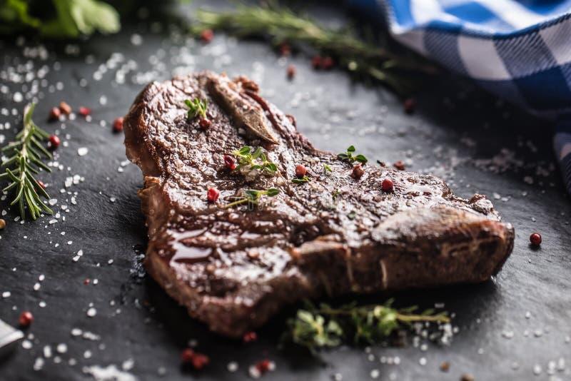 Bistecca nella lombata del manzo con il pepe ed i rosmarini del sale sulla piastrina dell'ardesia immagini stock libere da diritti