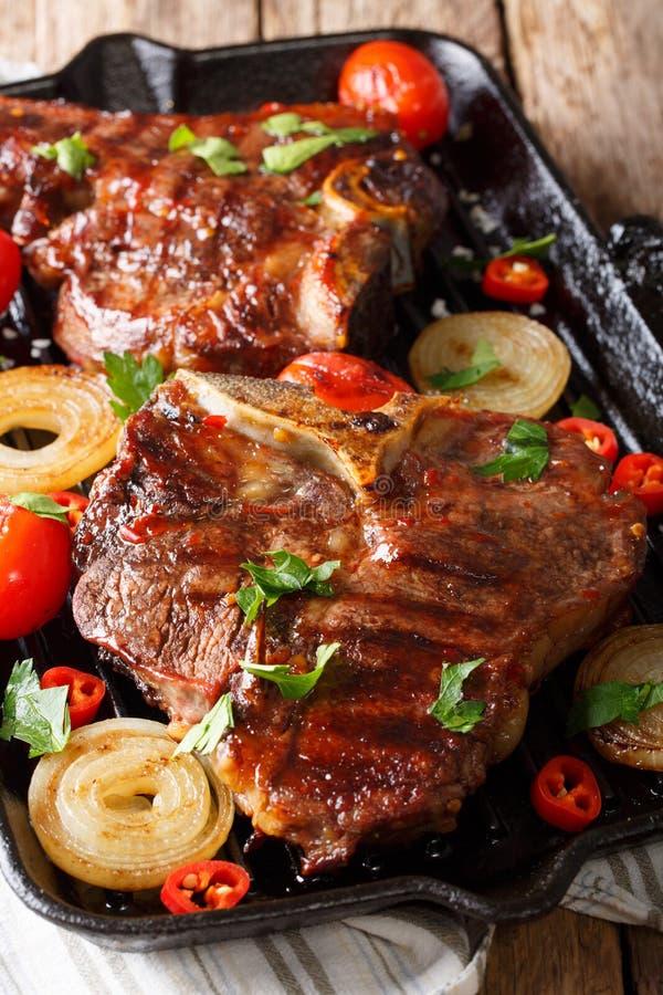 Bistecca nella lombata fritta con i pomodori, il peperoncino rosso e le cipolle in un PA della griglia fotografia stock