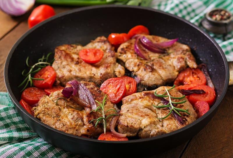 Bistecca succosa della carne di maiale con i rosmarini ed i pomodori fotografie stock libere da diritti