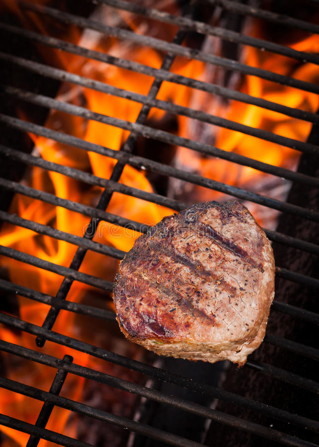 Bistecca sulla griglia ardente fotografie stock