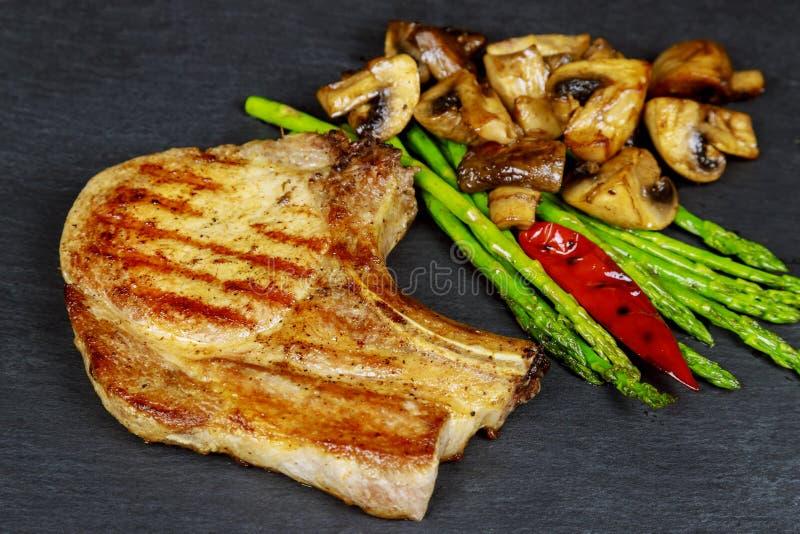 Bistecche arrostite della carne di maiale con le erbe, asparago, funghi sul fondo di pietra dell'ardesia fotografia stock