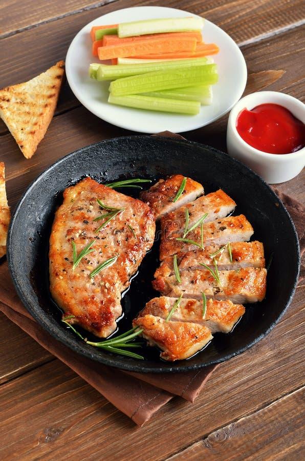 Bistecche cotte della carne di maiale in padella, salsa al pomodoro e sedano fresco fotografia stock libera da diritti