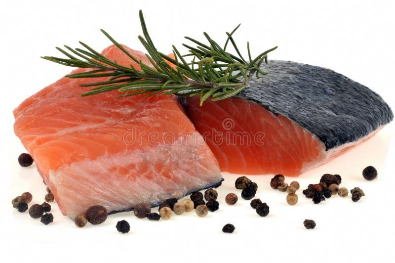 Bistecche di color salmone crude con i rosmarini e le spezie su un fondo bianco fotografia stock