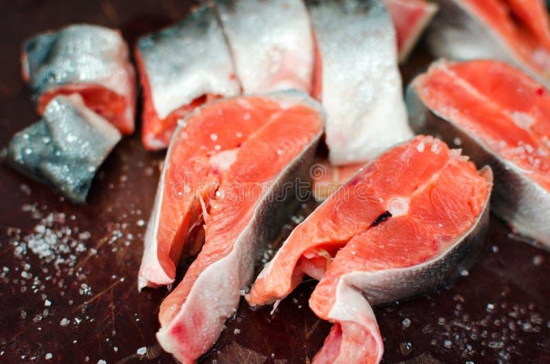 Bistecche di color salmone crude fresche con sale sulla tavola rustica fotografia stock libera da diritti