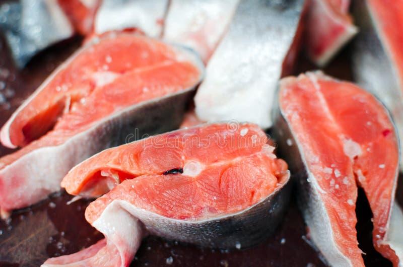 Bistecche di color salmone crude fresche con sale sulla tavola rustica immagine stock