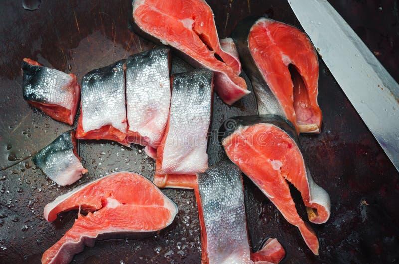Bistecche di color salmone crude fresche con sale sulla tavola rustica fotografia stock