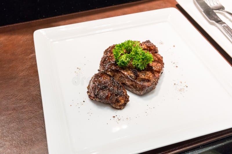 Bistecche di manzo arrostite con le spezie sul piatto bianco immagine stock libera da diritti