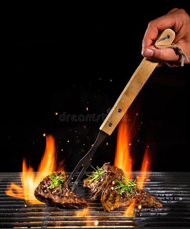 Bistecche di manzo che sono grigliate, isolato sul nero fotografia stock