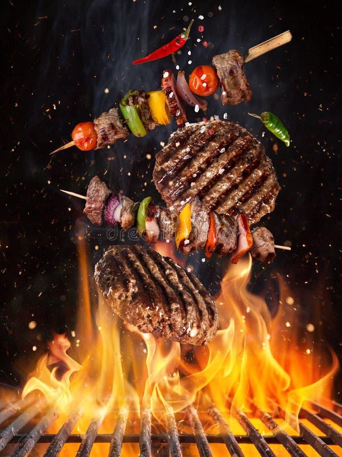Bistecche di manzo saporite e spiedi che volano sopra la griglia del ghisa con le fiamme del fuoco immagini stock