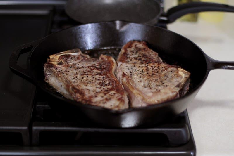 Bistecche di striscia di New York che cucinano in una pentola del ghisa immagini stock
