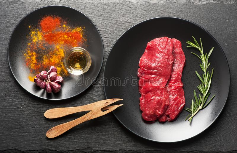 Bistecche, erbe e condimenti crudi di manzo fotografie stock