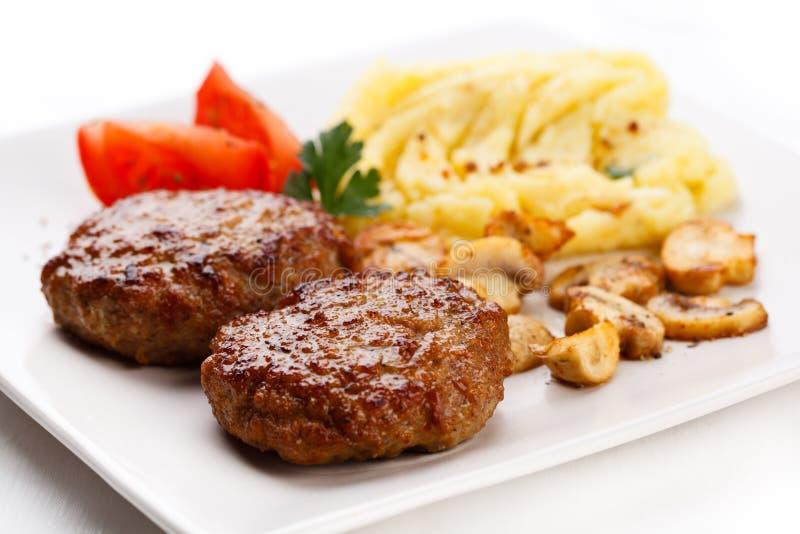 Bistecche fritte con le patate e funghi fritti immagini stock libere da diritti