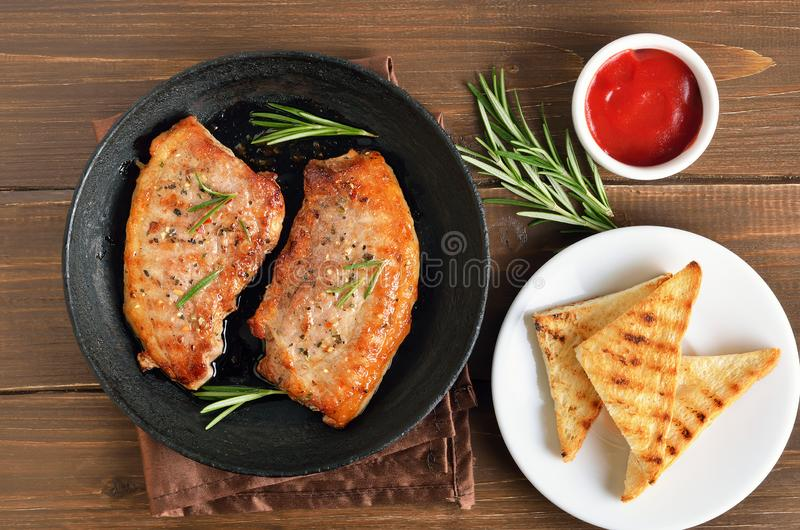 Bistecche fritte della carne di maiale in padella, pane tostato e salsa di pomodori immagine stock libera da diritti