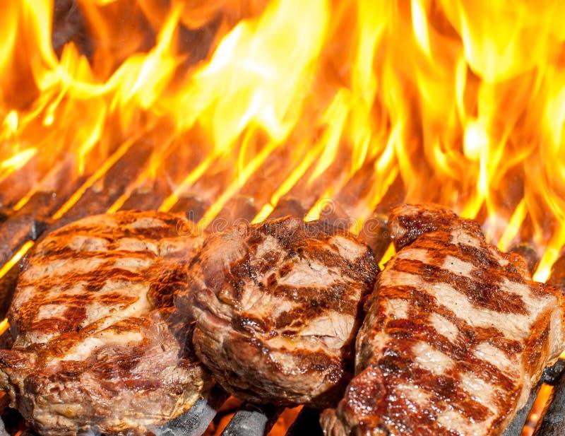 Bistecche sul cotte con le fiamme immagine stock