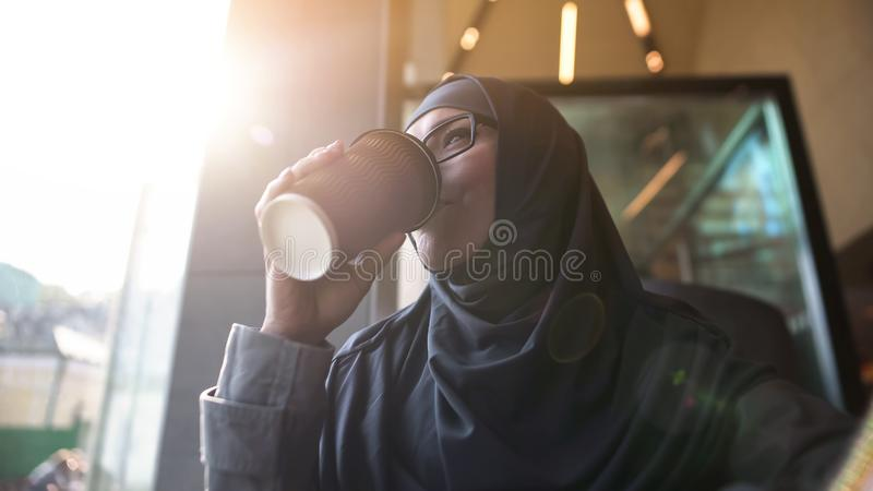 Bistrot di rilassamento beventi del caffè di bella signora musulmana, stile di vita moderno, svago fotografia stock