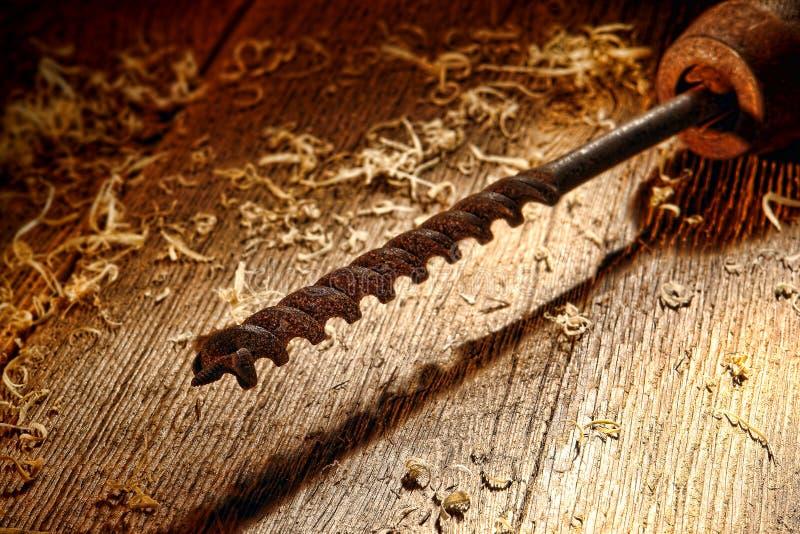 Bit de broca de madeira do vintage oxidado na placa de madeira antiga imagens de stock