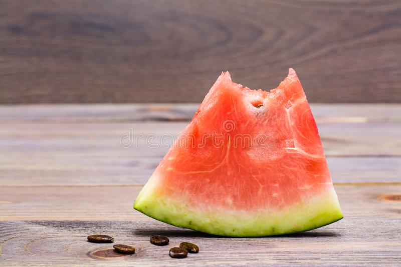 A bit of watermelon and watermelon seeds. On a wooden table royalty free stock photo