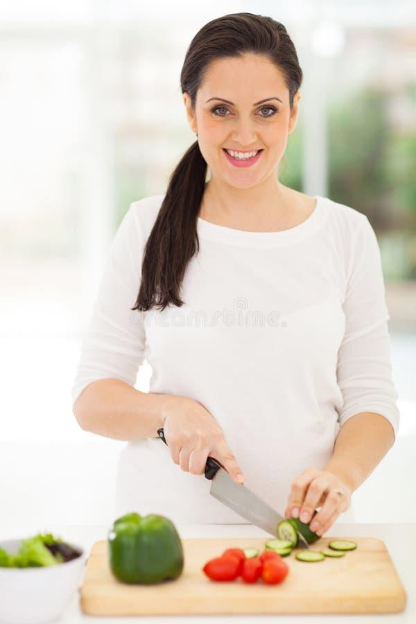 Bitande grönsaker för gravid kvinna royaltyfria bilder