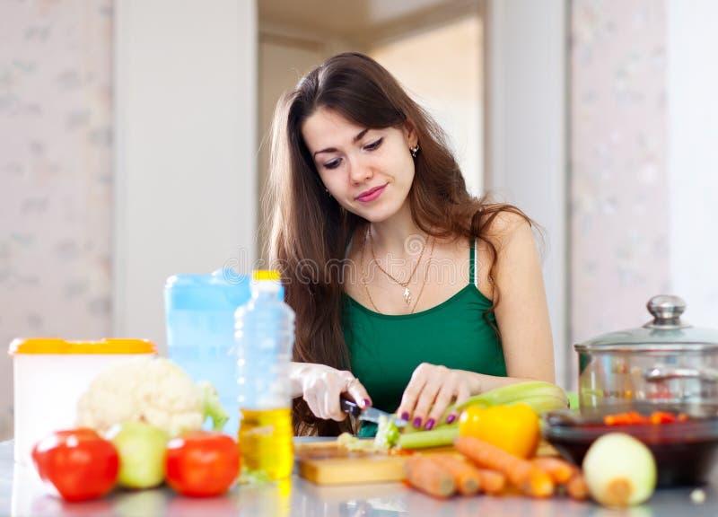 Bitande grönsaker för härlig hemmafru på kök royaltyfri fotografi