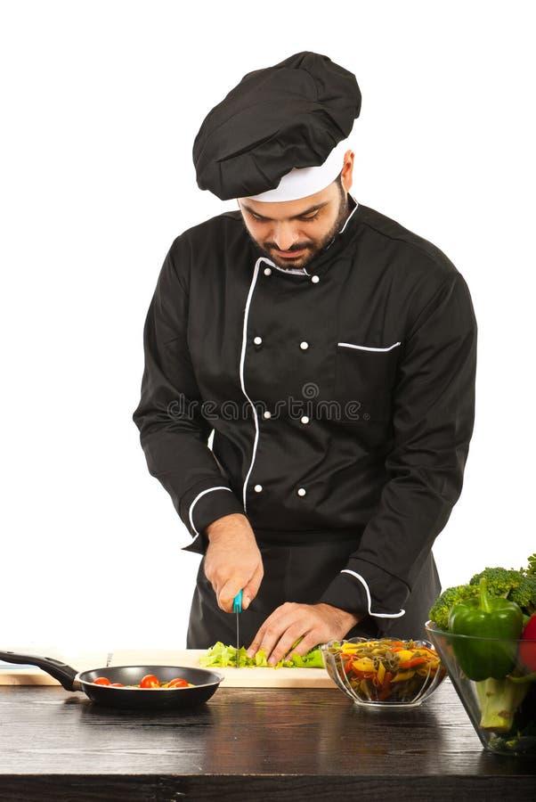 Bitande grönsaker för kockman royaltyfri bild