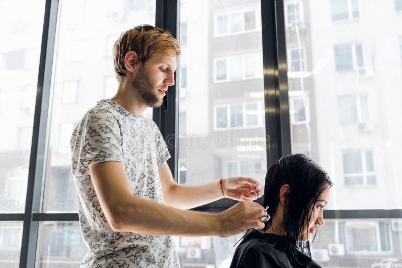 Bitande hår för frisör av en härlig allvarlig brunettkvinna arkivbilder
